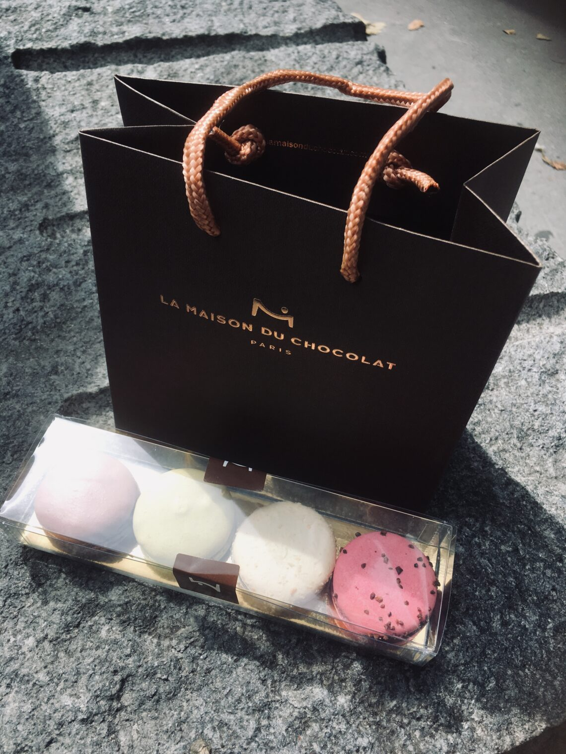 Macarons from la Maison du Chocolat, in a plastic holder, 4 different ones. A bag behind it from the store. Paris macaron walking tour