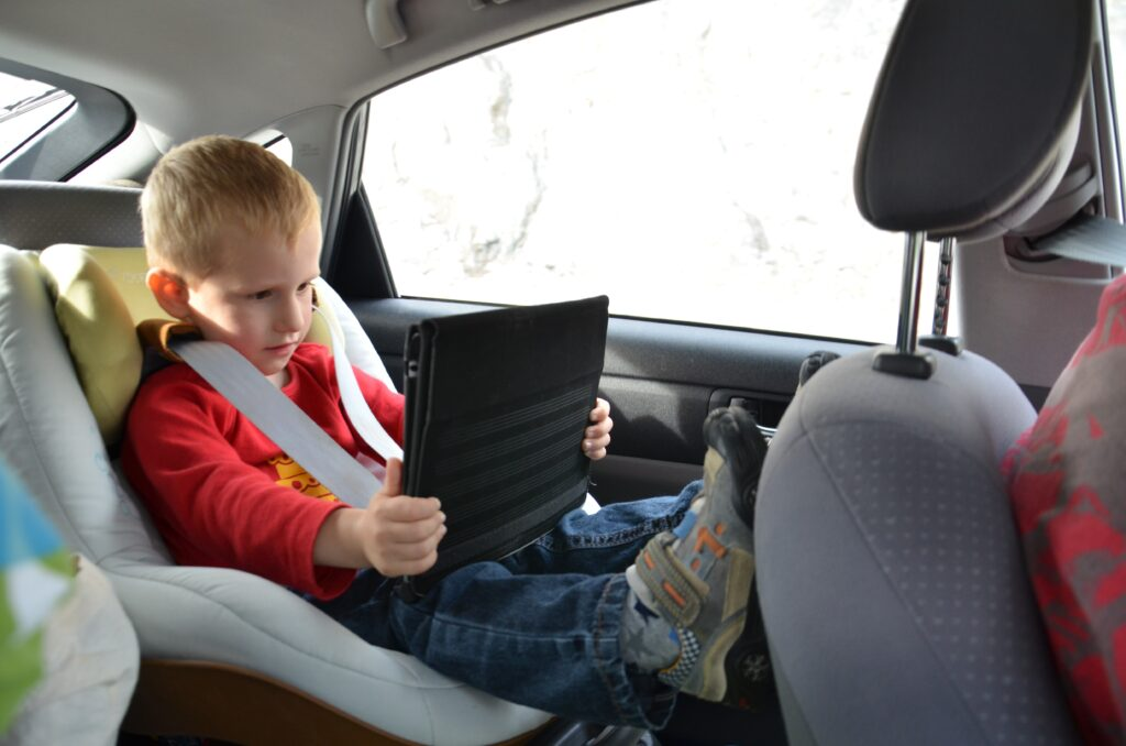Watching something on the tablet, Yuri sits in his carseat, arms and legs strechted