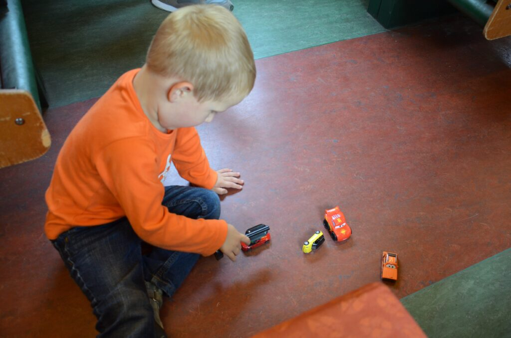 Favorite cars to play with, Yuri sitting on the ground playing with small cars in a train