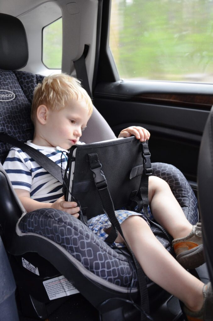 Yuri holding the portable DVD player, holding it in his hands while sitting in his car seat