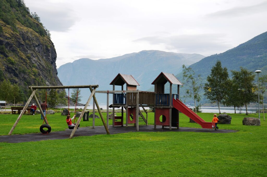 Playground in Norway Road trip with a toddler, stopping at a playground. Behind the playground is a Nordish fjord