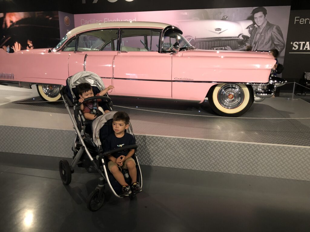 Graceland by JJ and the Bug, two kids behind eachother in a stroller in front of a pink cadillac in Graceland museum