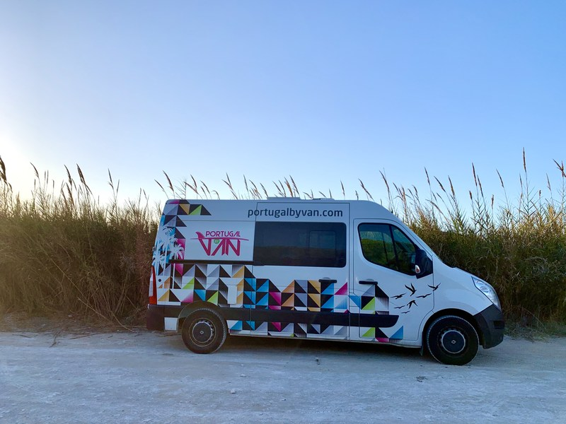 Road trip with a rental van by Beste voor Kids, van os in the middle of the picture, long grass field behind it, blue sky above, on a gravel road