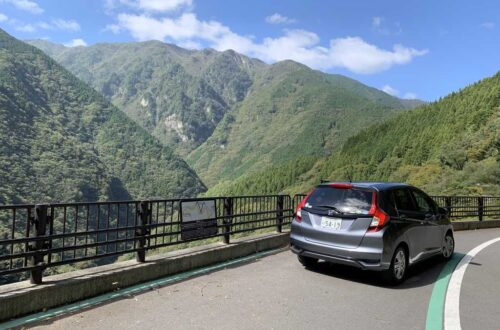 Driving during a road trip with a rental car by Beste voor Kids, car on the side of the road with beautiful mountain vista to the left