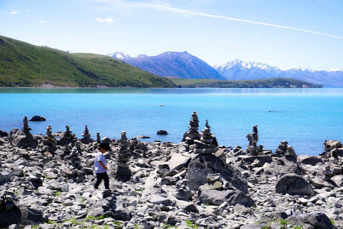 Lake Tekapo by Faraway Worlds, Road trip with a toddler, a toddler running between stones and a lake behind him with mountains in the back
