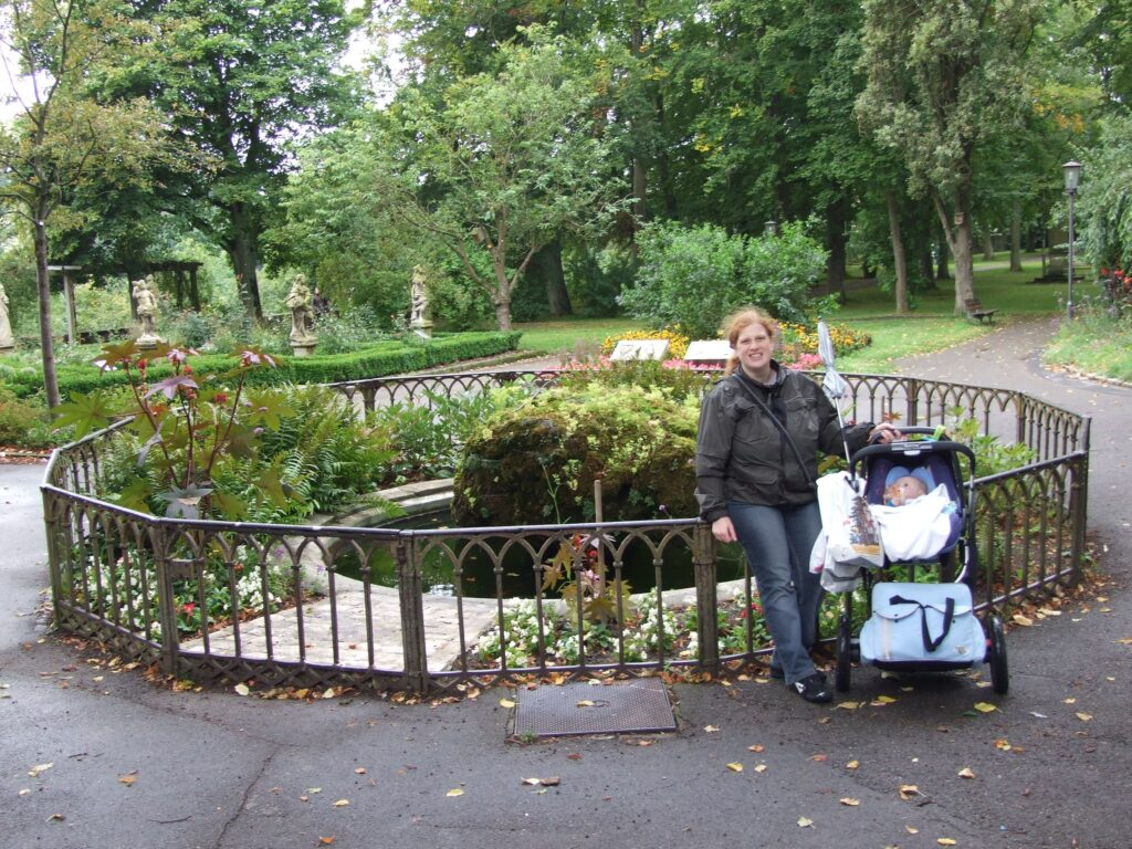The Maxi Cosi on the chassis, Cosette is standing next to it, with flowers and green behind her in a park