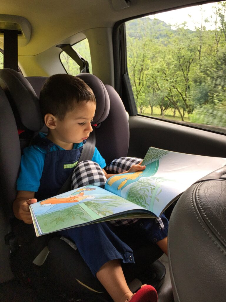 Toddler flipping through a book by Home Travel Guide