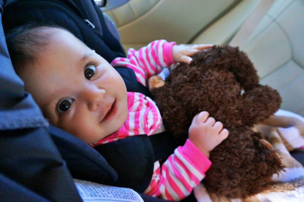 Baby in a car seat by WorldAdventurists, looking up and really adorable with a borwn stuffed animal