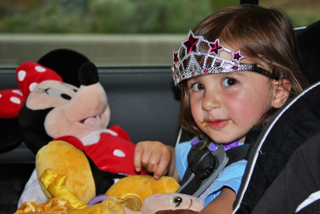 Playing in the back of the car by WorldAdventurists, a girl with a tiara in a car seat with a minnie doll