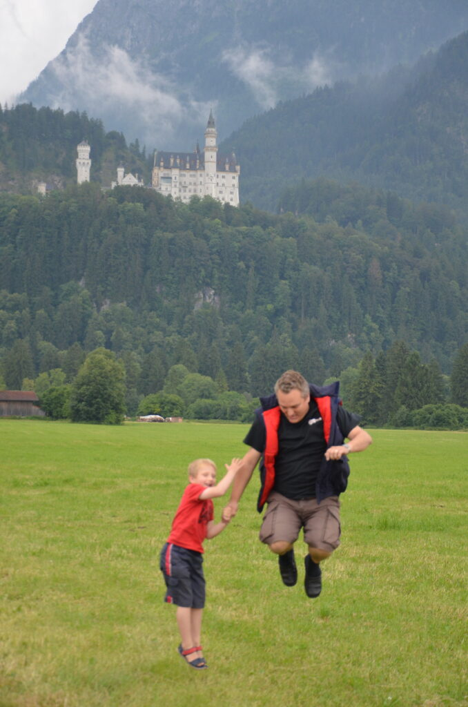 Jumping with Neuschwanstein castle in the back, Paul and Yur are jumping on a grass field