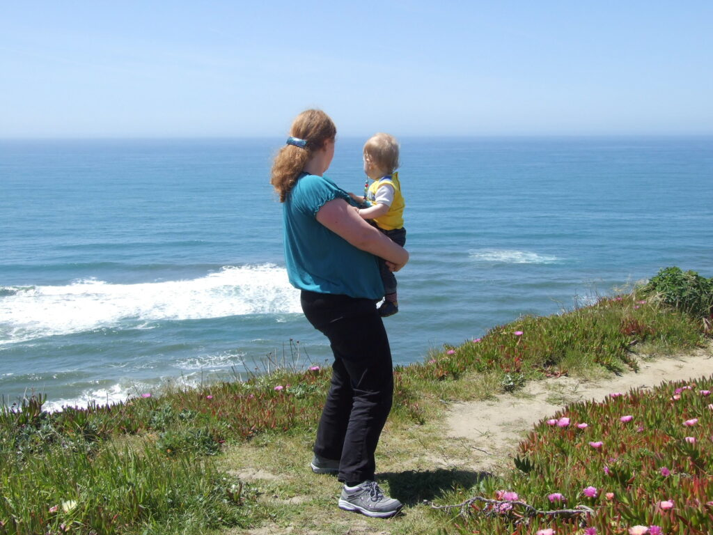 Enjoying the view at highway 1, Cosette holding Yuri in her arms on a cliff with the ocean below