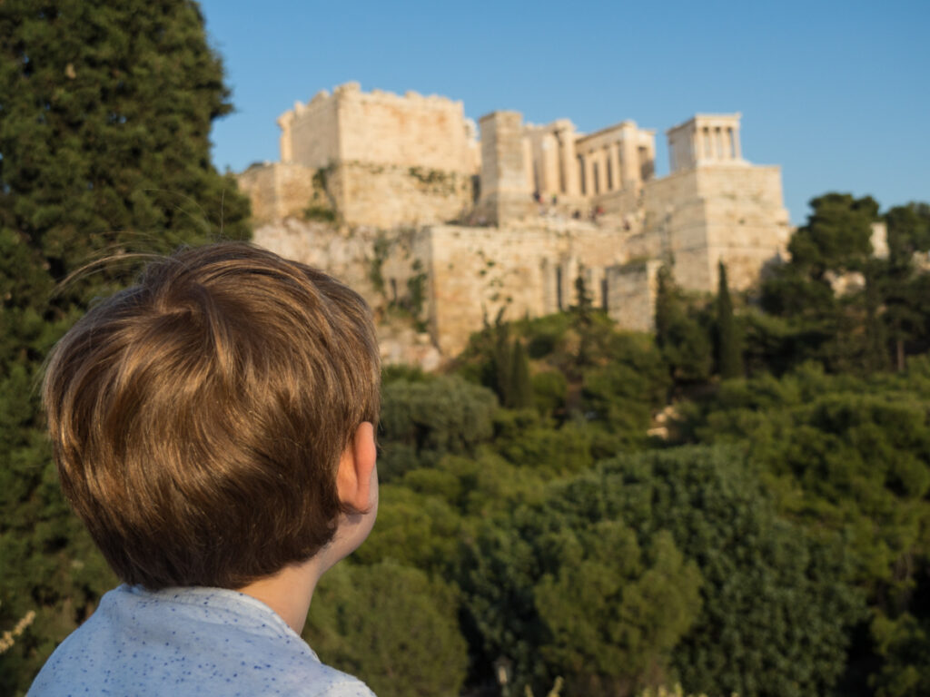 Athens with kids by The Family Voyage, A boy seen from behind, with a castle in the back and green trees all around