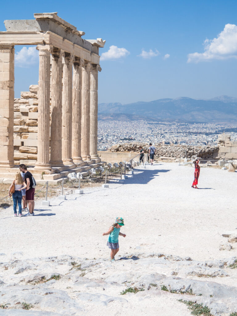Athens with kids by The Family Voyage, a child and other people are running around or standing near the Acropolis. Athens is visible in the backdrop behind it