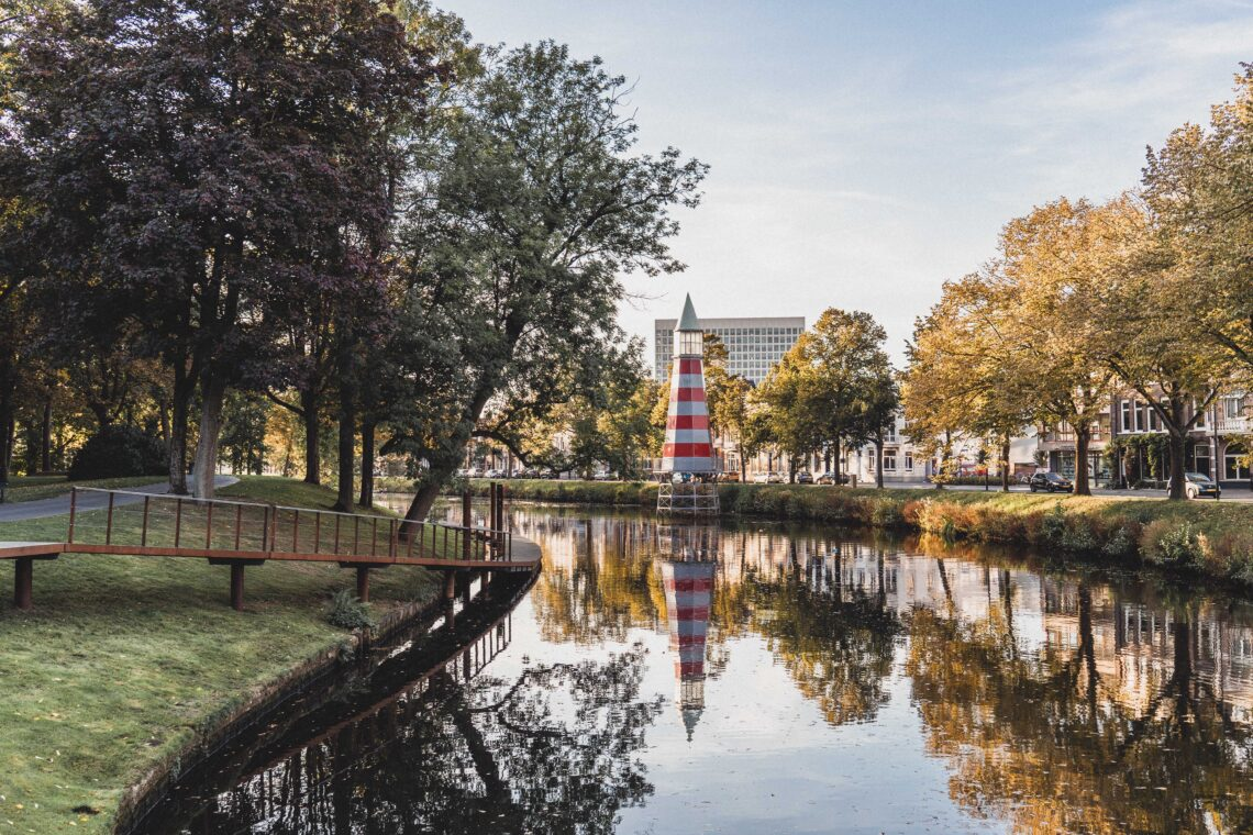 Breda by Solo Sophie, a canal, with on the left bank a park with grass and trees, on the rights trees and houses