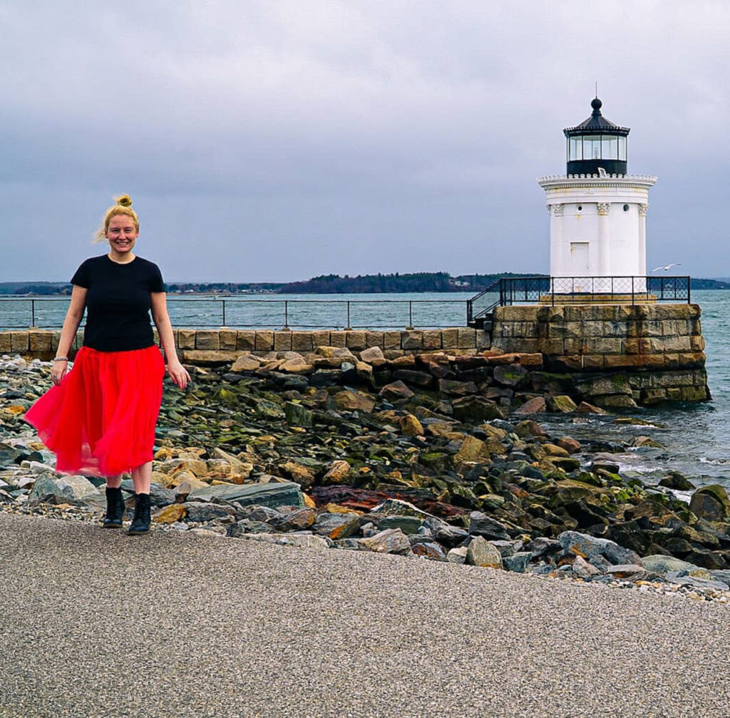 Bug Light in Portland Maine by Girl with the Passport, Kelly is standing on the left side of the picture, with a red skirt and a black top on. The lighthouse is on the right