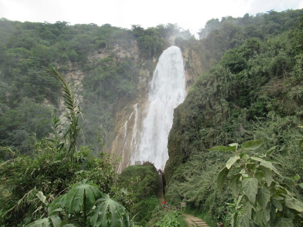 Cascades El Chiflon by Zoe Goes Places, a waterfall in the middle of the picture thundering down between lush green forest. A path is visible on the down right towards a viewpoint
