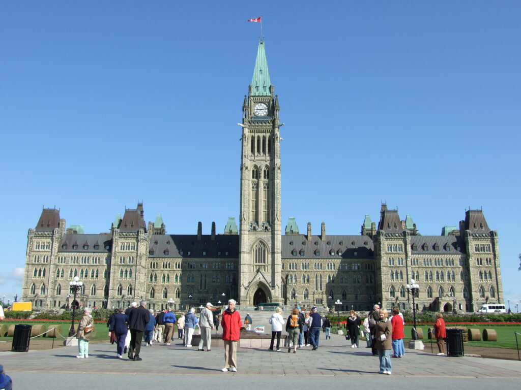 Parliament Hill at Ottawa, with people in front of it, admiring the building