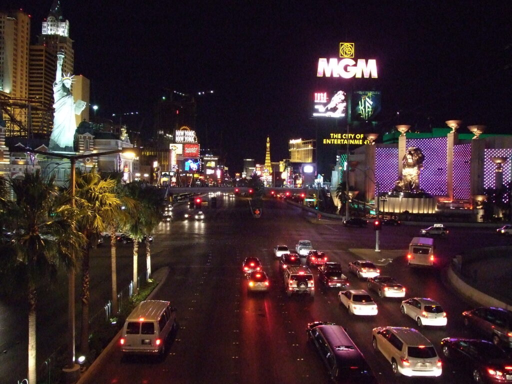 Las Vegas by night, cars on the broad street, buildings with lots of lights on both sides. A Replica Statue of Liberty to the left