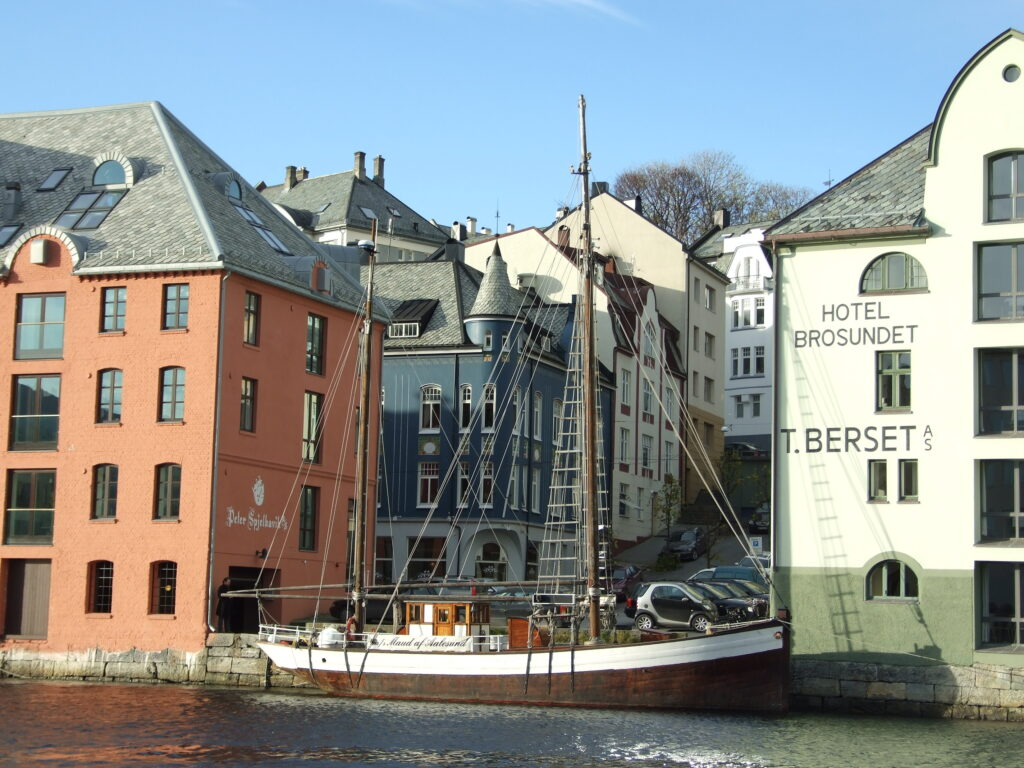 Alesund, a canal with a ship on dock and colorful buildings