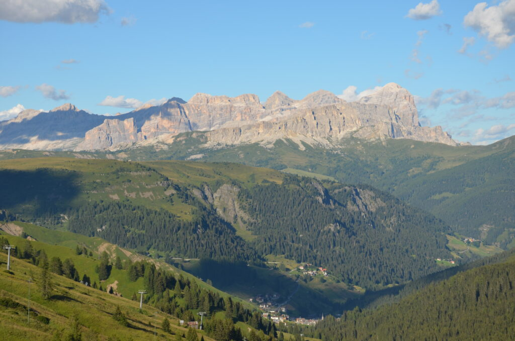 The Dolomites around Bolzano, green forest on the mountains and mountain peaks without trees. A clear blue sky above