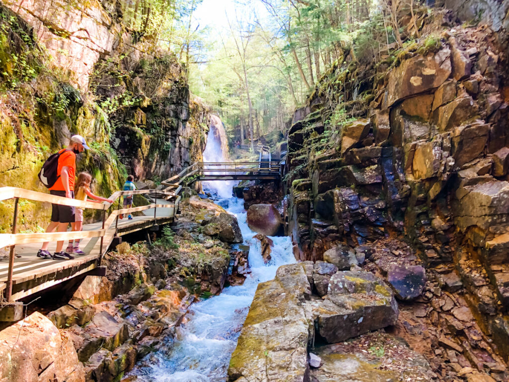 Flume Gorge by Bon Voyage with Kids, a gorge with on the left a walkway suspension with people on it. In the middle the river and waterfall, a bridge a little further in the back