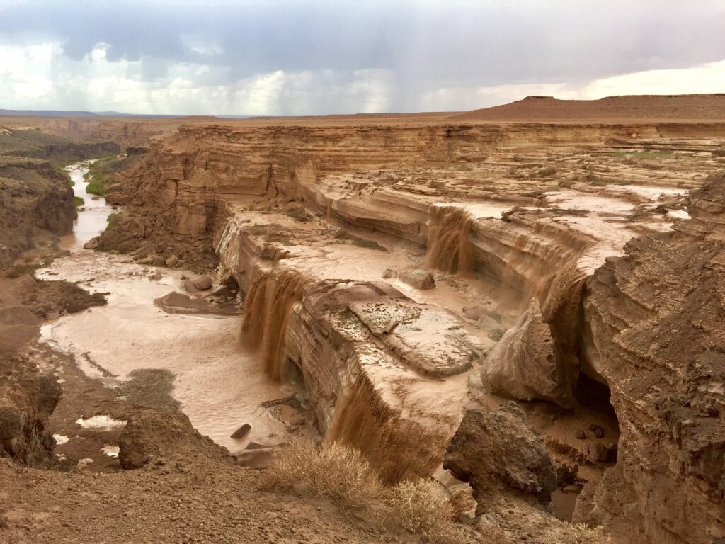 Grand Falls by Danielle Outdoors, a chocolate colored waterfall flowing and dropping down several tiers, the surroundings is also brown colored