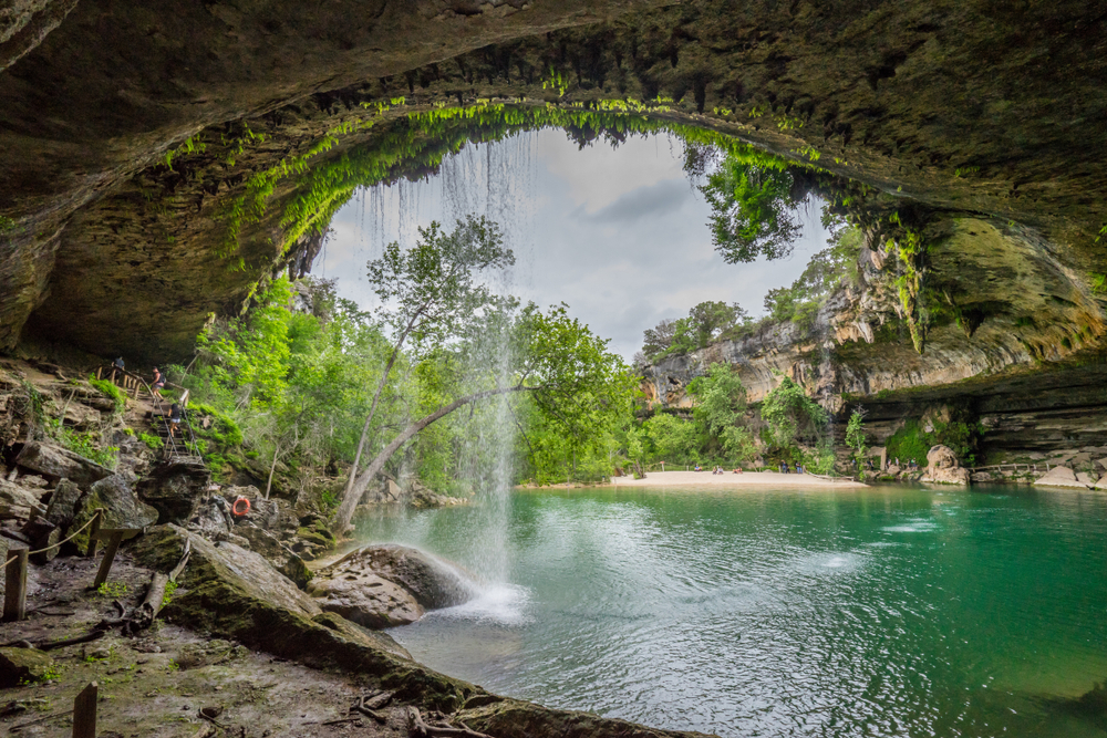Hamilton Pool Preserve by Texas Travel 365, seen from behind the waterfall. It flows/plunges down a cliff in a pool