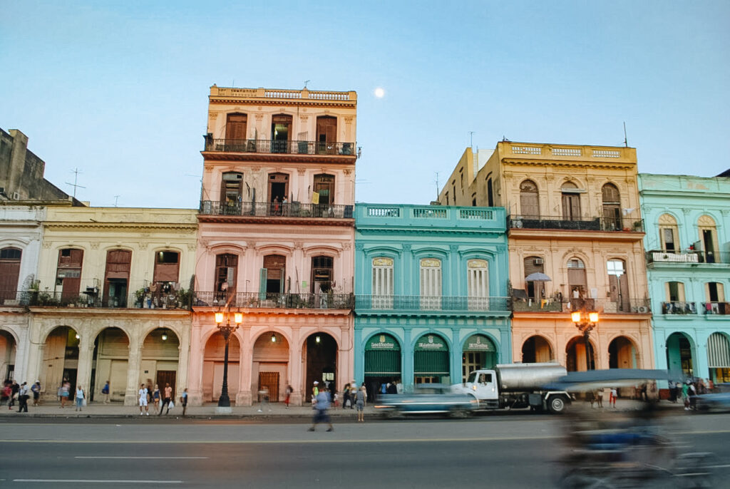 Havana by Home to Havana, old buildings in different colors, in front a street with some cars, a riksja and people all around