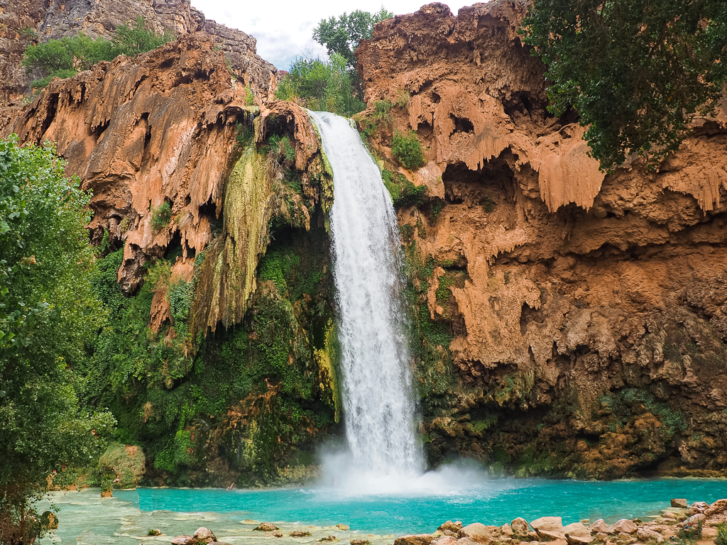 Havasu Falls by Traveling Found Love, a waterfall drops over a cliff, in a really turquioise/blue pool