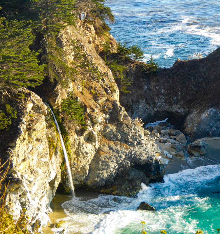 McWay Falls by Roadtripping California, a waterfalls plunges down in the ocean. Seen from a viewpoint. With a wild coast surrounding it