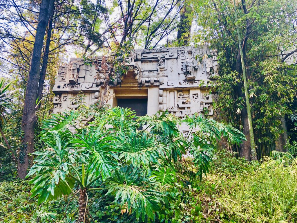 Mexico City Anthropology-Museum by Travel Mexico Solo, behind scrubs and trees is an old building, the museum