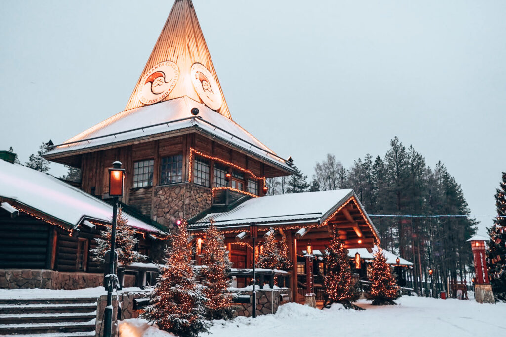 Rovaniemi, Santa's Village by Ronja Goes Abroad,  covered in snow is a building with a low roof up front and a tower in the middle, lower roofs on all sides
