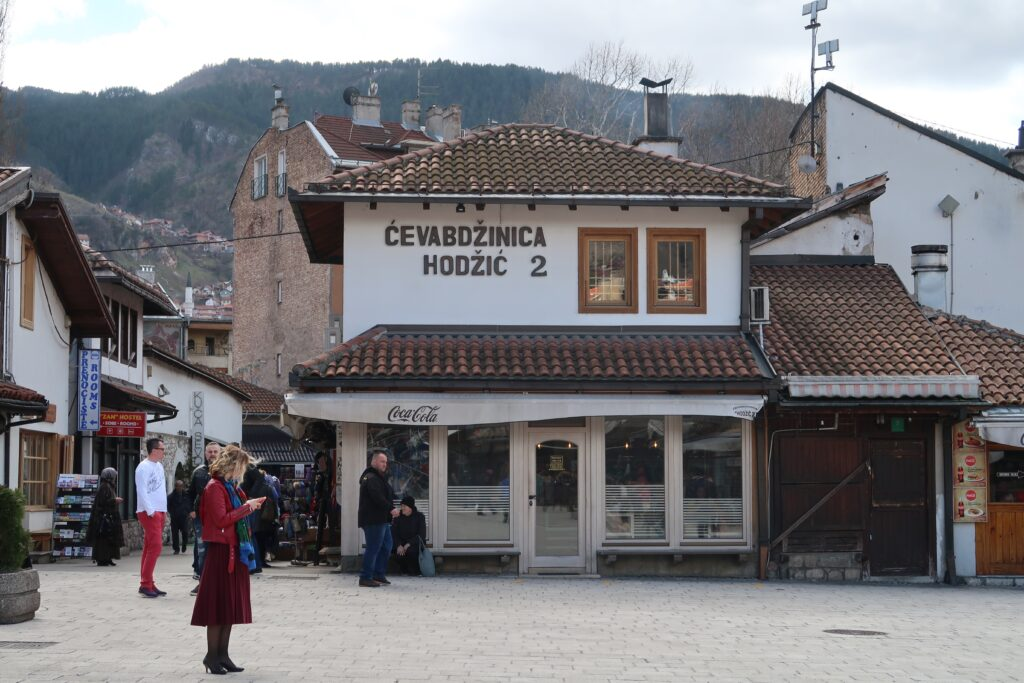 Sarajevo by Hey Explorer, a street with one building in the middle, and parts of buildings to the sides