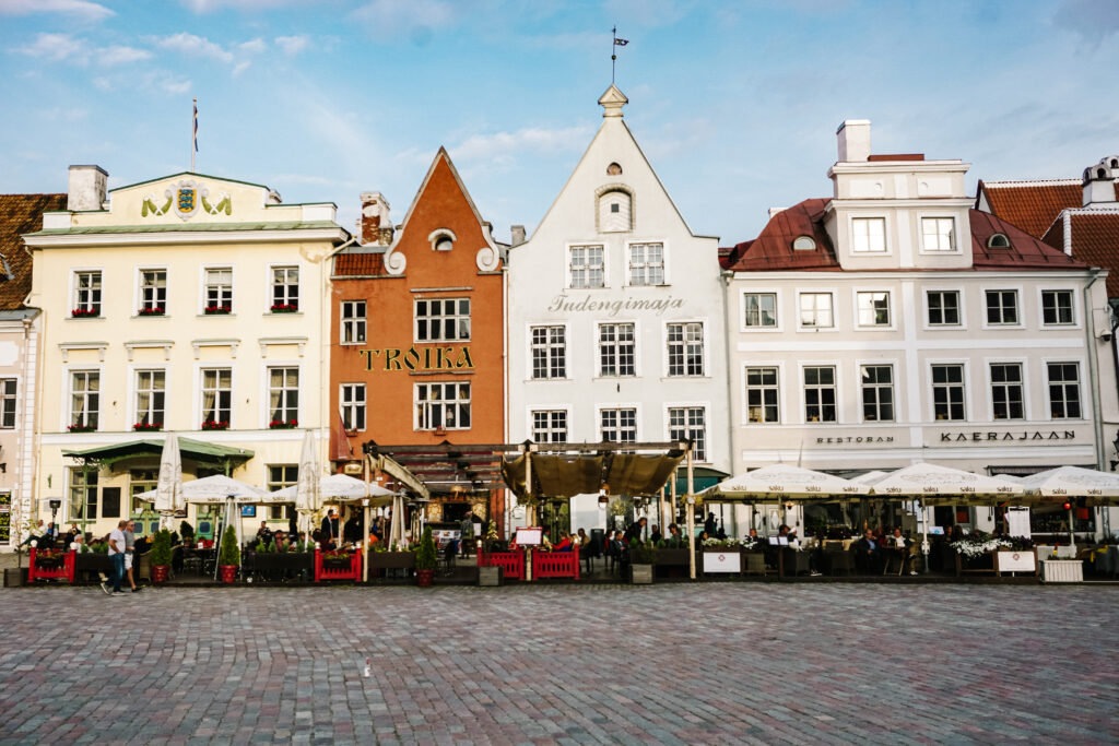 Tallinn by Passport the World, a square with white and an oker yellow houses at the square, with terraces and stalls in front
