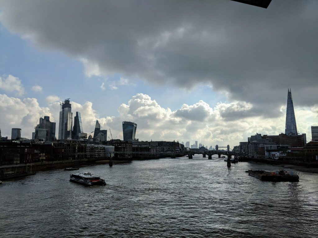 Thames River by Adrenaline Junkiez, , the Thames roiver, with on both sides the banks with houses and the skyline of LOndon, with a clowded sky