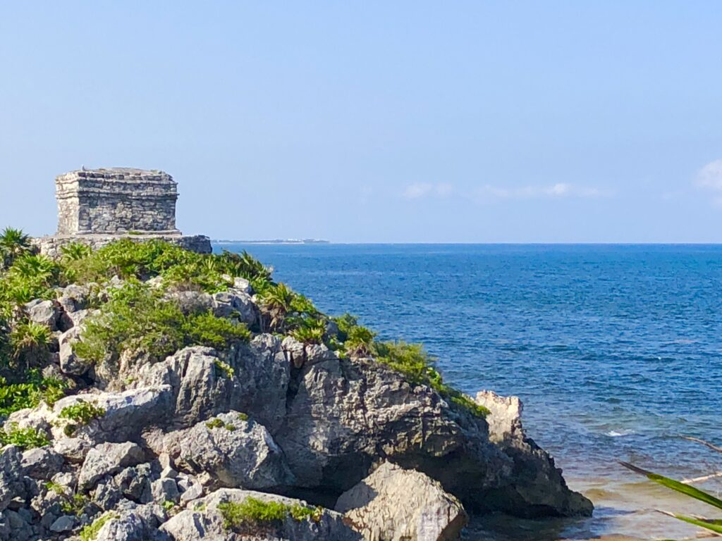Tulum Ruins by Travel To Merida, the seato the right, with a ruin on top of rocks with grass on the left