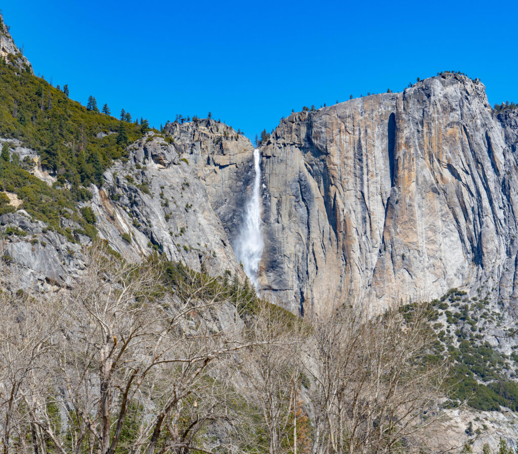 Yosemite Falls by Bae Area & Beyond, as seen from afar. In the back a waterfall plunges down from  a cliff