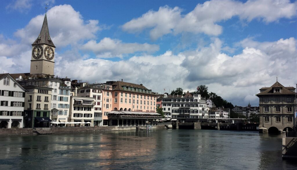 Zurich by Walk a While with Me, a skyline above a river of Zurich
