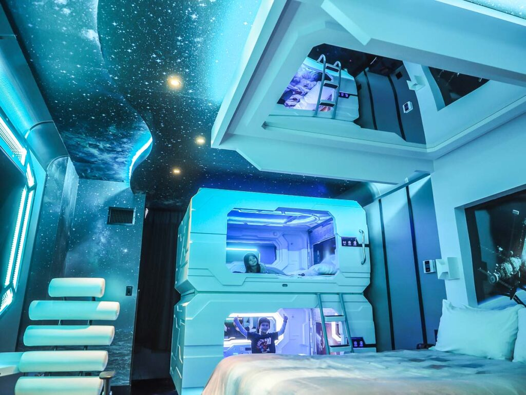 Space themed room Fantasyland Hotel at Edmonton by Fun World Facts, a hotel room in Space theme, with neds and a bunk bed, with a girl and boy on the beds