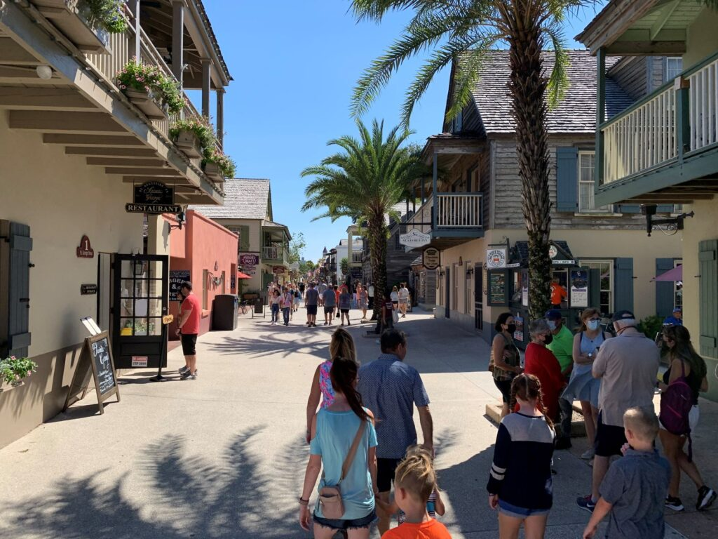 St Augustine historic downtown by DavidnBrace, people walking on a street in down town, restaurants and shops on both sides and palm trees